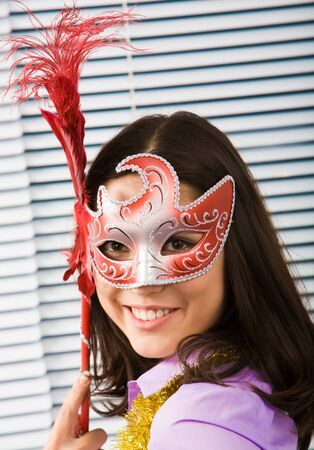 Portrait of beautiful girl wearing carnival mask and looking at camera photo
