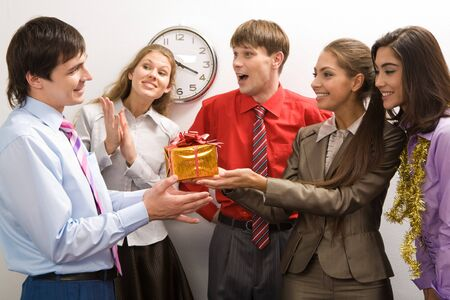 holiday gathering: Portrait of friendly colleagues giving birthday present to happy man in office Stock Photo
