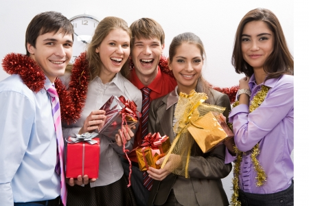 Happy businessgroup with colorful presents in hands looking at camera and smiling