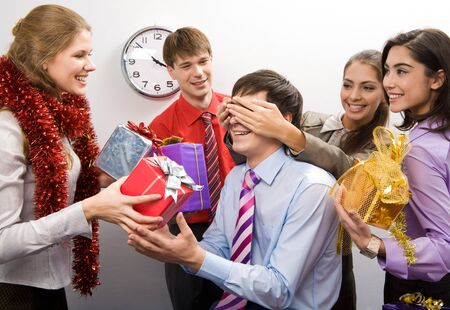and guessing: Photo of cheerful businesswoman keeping her hands on man�s eyes while their colleagues preparing gifts for him