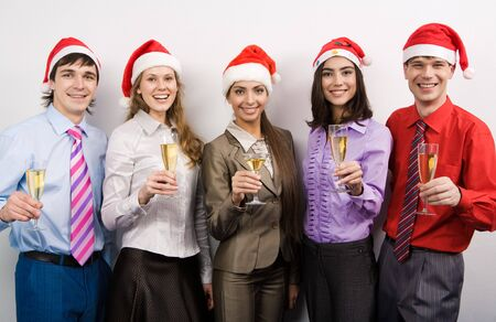 Portrait of joyful co-workers in Santa caps and champagne in hands looking at camera with smiles photo