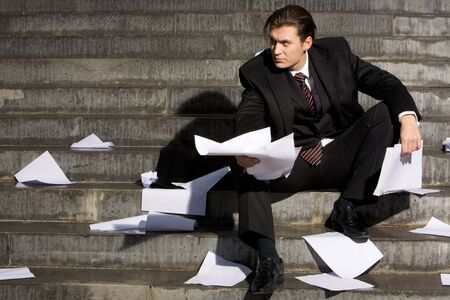 loss leader: Photo of attractive businessman sitting in frustration with papers in hands
