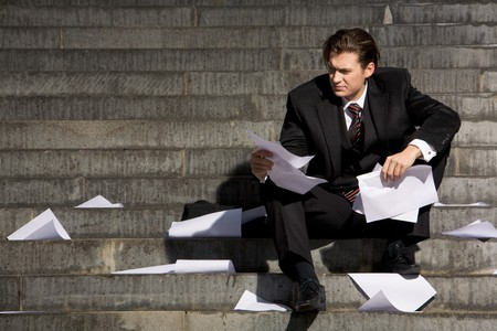 Unhappy businessman suffering from world financial crisis while sitting on stairs Stock Photo - 3968205