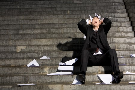 woe: Despaired businessman screaming with papers in hands while sitting on staircase