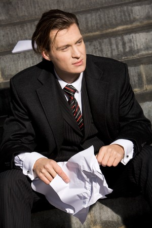bore: Portrait of handsome business leader with crumpled piece of paper in hands
