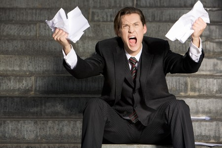 expressing: Photo of screaming businessman with two sheets of paper in his hands