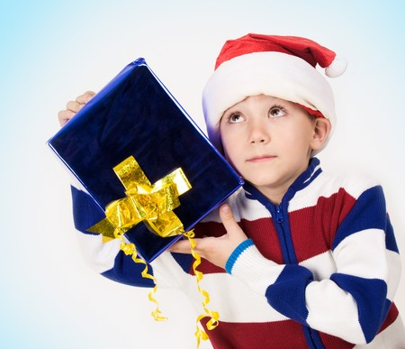 Portrait of cute boy with giftbox in hands and listening to something in it photo