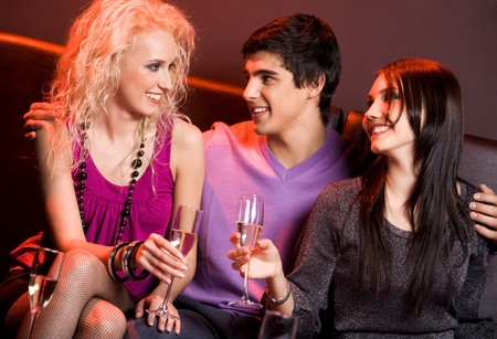 Photo of happy guy between two pretty girls chatting at xmas party Stock Photo - 3997630