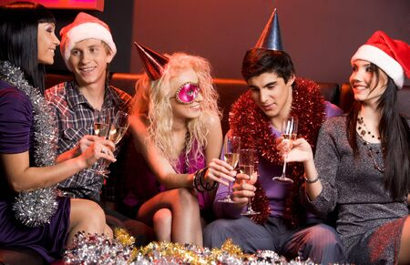 Portrait of smartly dressed young people communicating at festive table in night club photo