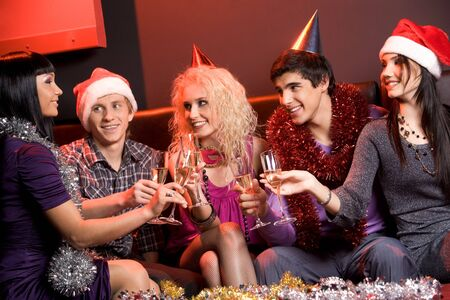 Portrait of boozing people wearing holiday clothing and toasting at xmas party photo