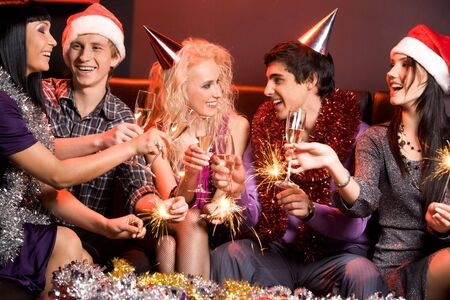 Cheerful friends having fun and enjoying themselves at new year party photo