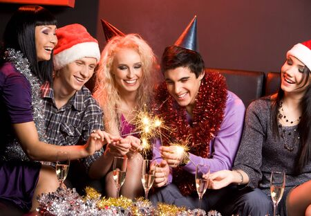 male friends: Group of friends looking at sparkling Bengal lights and laughing Stock Photo