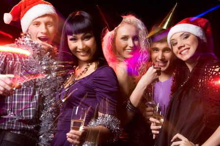 party friends: Photo of cheerful people looking at camera with smiles while enjoying Christmas party