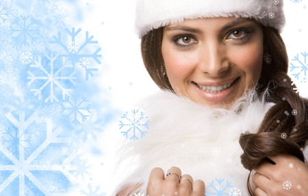 Face of pretty woman surrounded by flakes touching white fur  photo