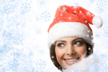 Face of smiling woman in Santa cap looking out of snowflakes  photo