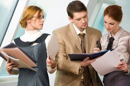 Portrait of confident associates looking at business document and reading it before signing photo