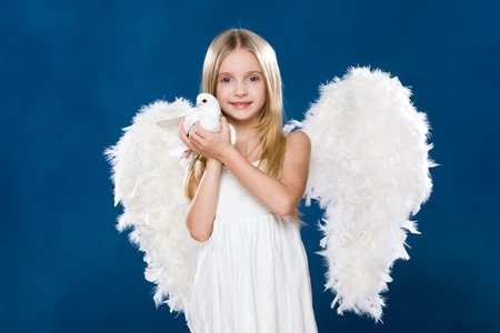 Portrait of glad angel holding white dove in hands and looking at camera Stock Photo
