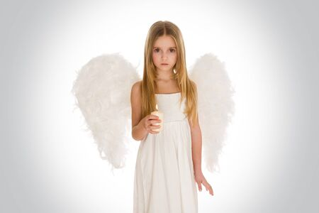 Portrait of innocent girl with candle and wings surrounded by holy light looking at camera photo