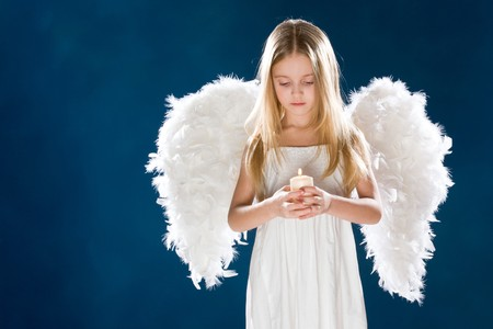 Portrait of peaceful girl wearing white wings looking at candle in her hands over blue background photo