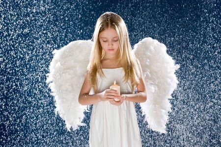 Photo of sad angel holding burning candle while standing under snowfall Stock Photo - 4032963