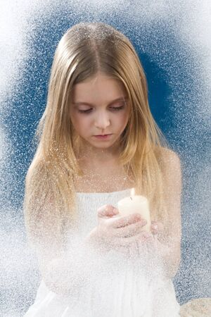 flurry: Image of praying girl looking at burning candle in her hands behind frosty window