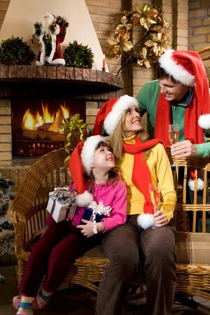 Portrait of happy family wearing santa caps while sitting by fireplace and looking at each other Stock Photo - 4032965