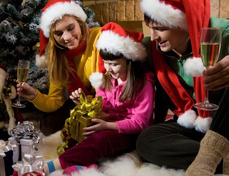 Photo of happy family members looking at nice giftbox in girl's hands who is going to open it photo