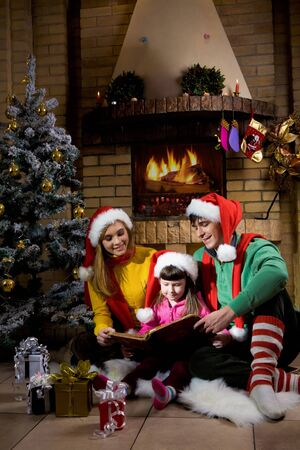 navidad navidad: Portrait of family spending Christmas evening at reading book by fireplace