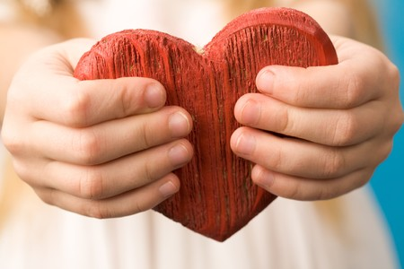 with fondness: Close-up of red wooden heart in child�s hands showing it
