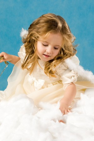 Photo of pretty girl in angelic costume on a blue background   photo