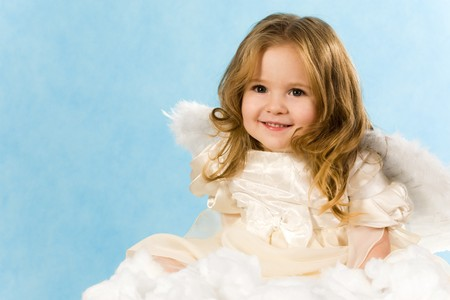 angel alone: Happy little girl wearing angel dress sitting on white cloud and smiling