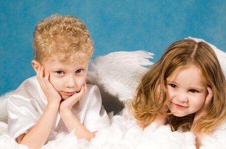 Fotos de los pequeños niños y niñas en vestidos de ángel mentir sobre nube blanca, y teniendo en resto Foto de archivo - 4032920