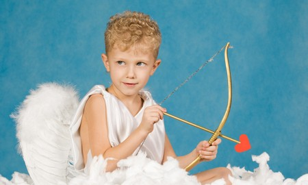 Portrait of little boy with bow and arrow ready to make someone fall in love photo