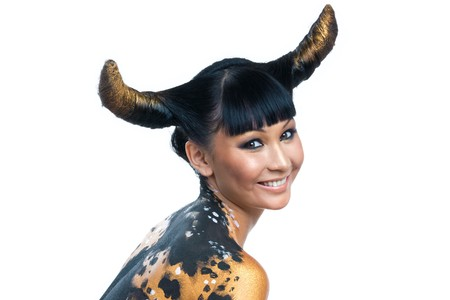 bodypaint: Portrait of joyful female with golden makeup and horns on head looking at camera with smile Stock Photo