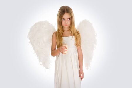 Portrait of innocent angel with burning candle looking aside photo
