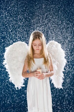 angel girl: Portrait of calm girl wearing angel wings and holding candle in flurry snowfall