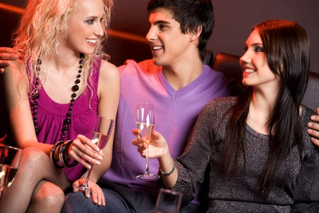 Portrait of smart young people holding champagne flutes and chatting with each other Stock Photo - 4113756