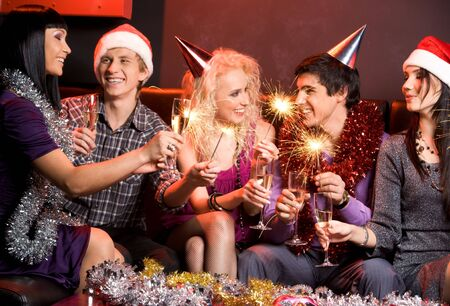 Portrait of happy guys and girls enjoying New Year party with champagne and Bengal lights photo