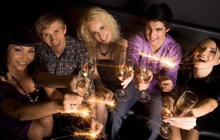 View from above of joyful friends with champagne and sparkling lights in hands during celebration photo