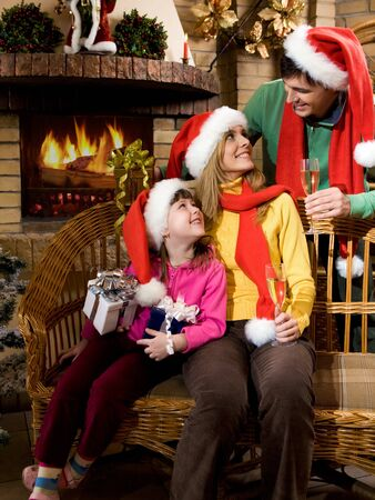 Portrait of happy family wearing santa caps while sitting by fireplace and looking at each other photo