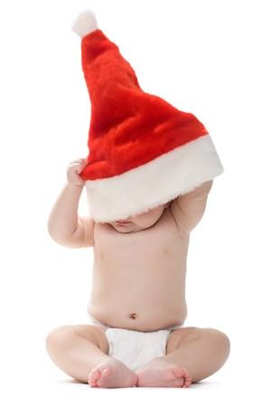 xmas baby: Photo of cute baby hiding his head inside Santa cap while sitting on the floor