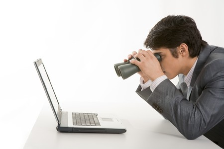 Portrait of businessman holding binoculars and looking at laptop  photo