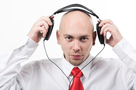 Portrait of serious male putting headphones on his head and looking at camera photo