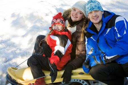 Portrait of sports family sitting on the sleigh together  photo