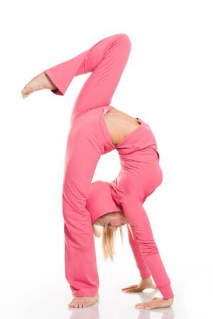 Profile of skillful female wearing pink sportswear doing aerobics over white background photo