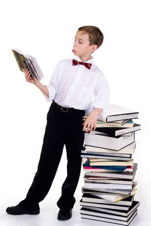 Portrait of astonished schoolboy looking at textbook with stake of books near by  photo