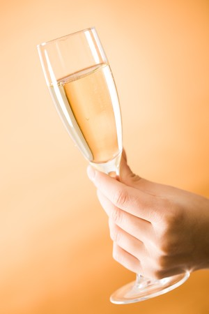 Image of female hand holding champagne on orange background  Stock Photo - 4192945