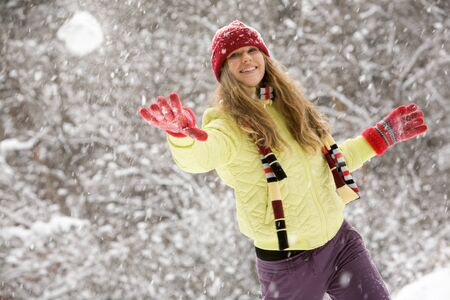 Image of attractive young woman flinging the snowball  photo