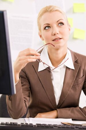 Portrait of pensive businesswoman sitting at workplace  photo