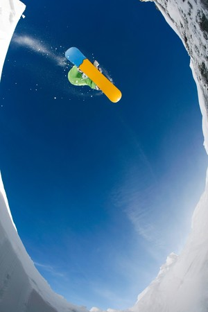 Below view of sportsman enjoying snowboarding on background of blue sky photo